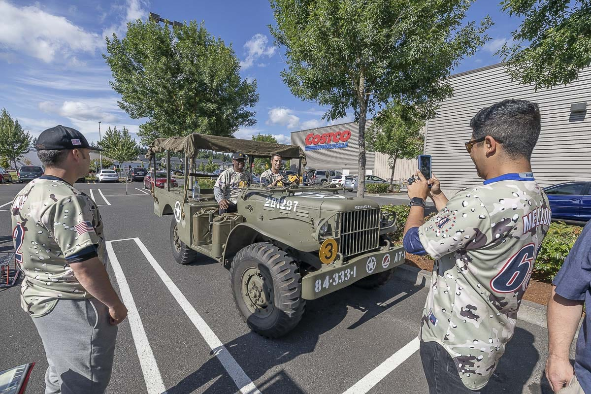 Current members of the military pose with some vintage military equipment during Heroes Night on Saturday at the east Vancouver Costco. They are also athletes, part of the U.S. Military All-Star baseball squad that begins its summer tour this week in Clark County. Photo by Mike Schultz