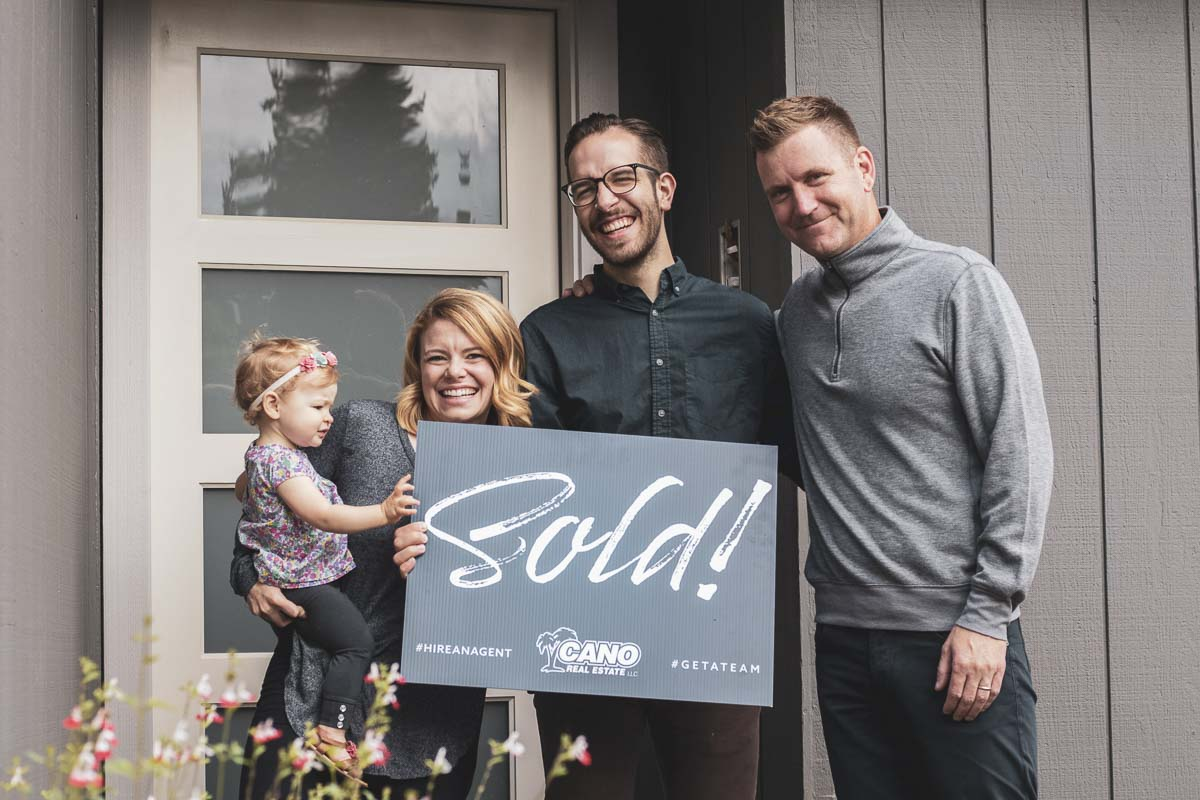 Garrett and Becca Olmstead, owners of The Locksmythe Salon in downtown Vancouver, are shown here in front of the new home they purchased just last week, thanks to the help of Cano Real Estate agent Kelly Winn (right). Photo courtesy of Ryanne Pitts