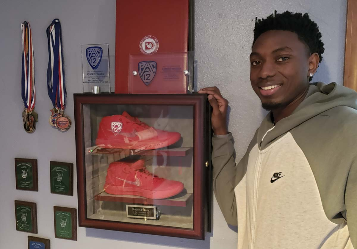 Robert Franks Jr. stands next to the display that his father made for the family home in Vancouver. Those are the shoes Junior wore when he made a school-record 10 3-pointers for the Washington State Cougars. Photo by Paul Valencia