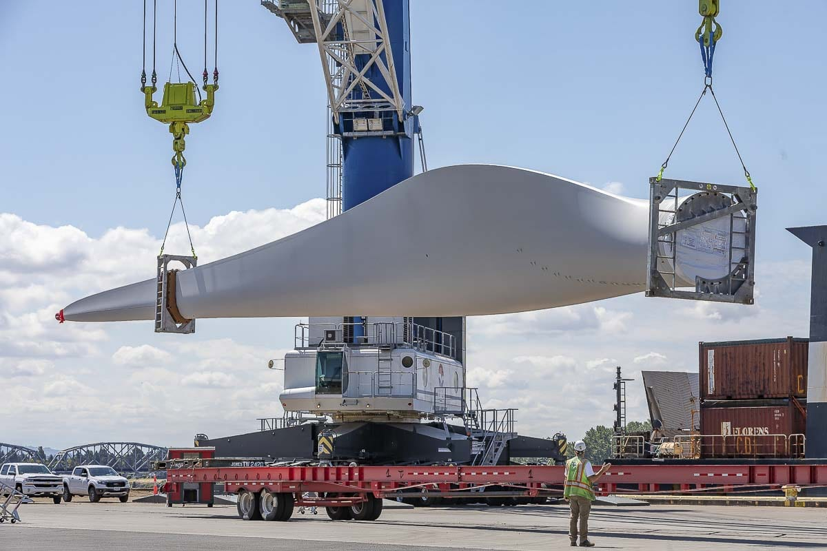 Crane operators at the Port of Vancouver, lower a 161-foot wind turbine blade onto a long flatbed truck for transport. Photo by Mike Schultz