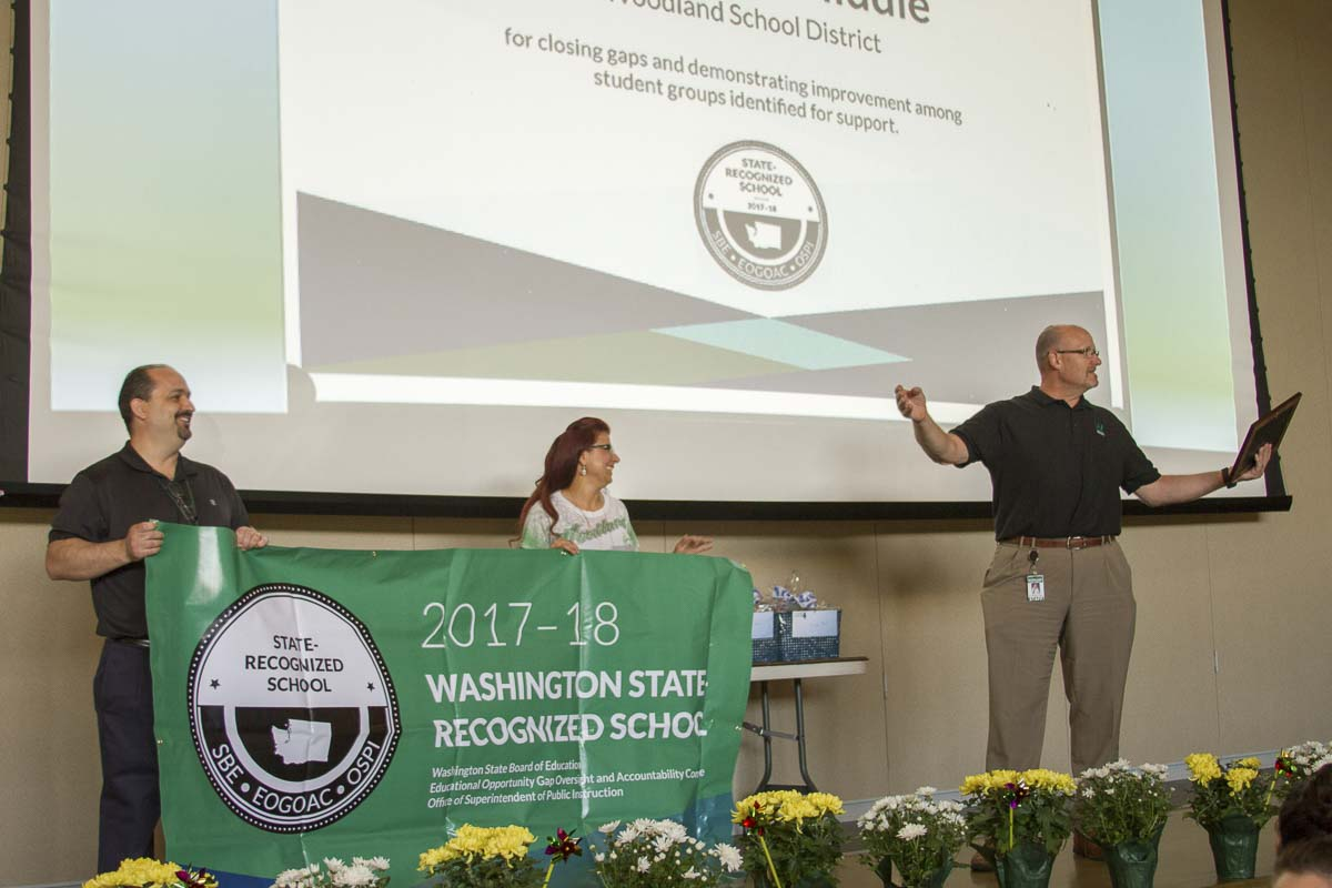 Principal James Johnston (left) received a banner and plaque for Woodland Middle School from Assistant Superintendent Asha Riley (center) and Superintendent Michael Green (right) during the district's annual end-of-year staff celebration on June 12. Photo courtesy of Woodland School District