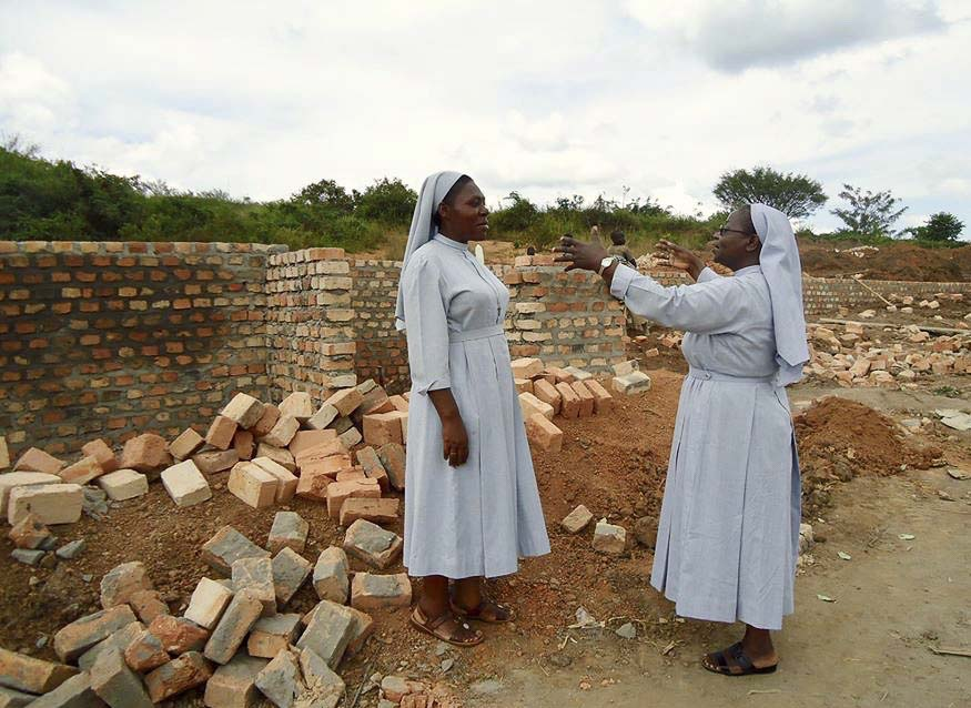 Sister Elizabeth Namazzi is shown here, explaining to a fellow nun how the Center for Early Mothers will be laid out over three buildings. Photo courtesy of Sister Elizabeth Namazzi