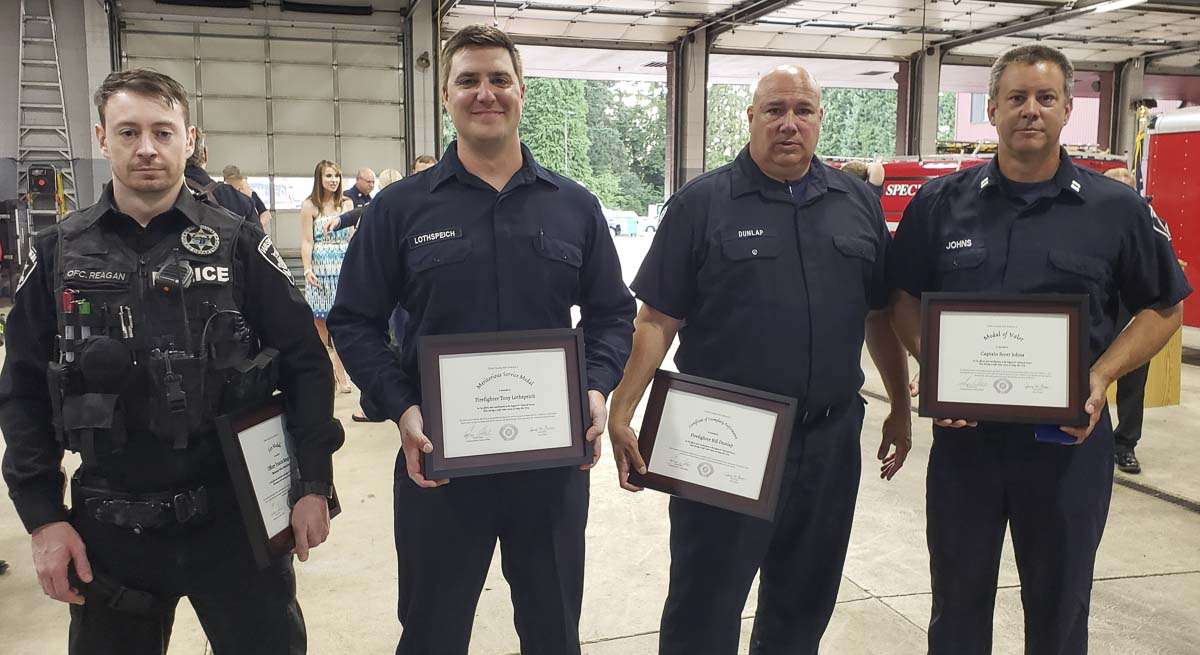 Washougal police officer Francis Reagan, firefighters Tony Lothspeich and Bill Dunlap, and Captain Scott Johns, were recognized Tuesday by Clark County Fire District 6 for their heroic actions in saving a woman from drowning in the Washougal River in May. Photo by Paul Valencia