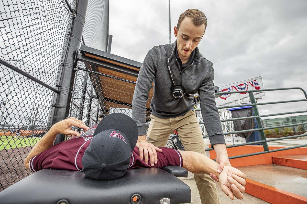 Mason Trezise gets in some maintenance work on Dominic Enbody before a Ridgefield Raptors game. Trezise is the team's athletic trainer. Photo by Mike Schultz