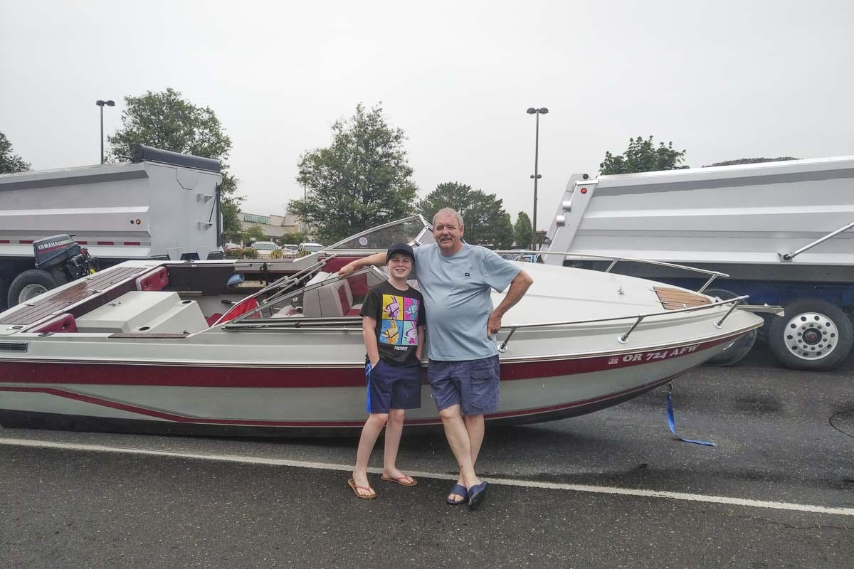 Jack Maynor (right), who had been behind the wheel of the truck towing the boat at the time of the accident, is shown here in front of the strange scene with a family member. Photo by Michael McCormic, Jr.