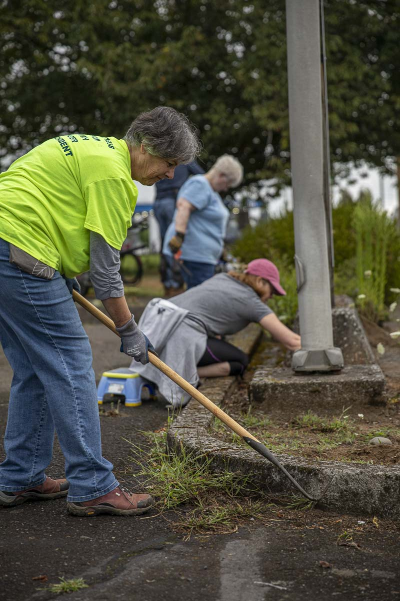 Su Scott (front), Bryn Howell (next back), and Nancy Wilson (last back) clean out garden beds at the Inter-Faith Treasure House in Washougal. Photo by Jacob Granneman