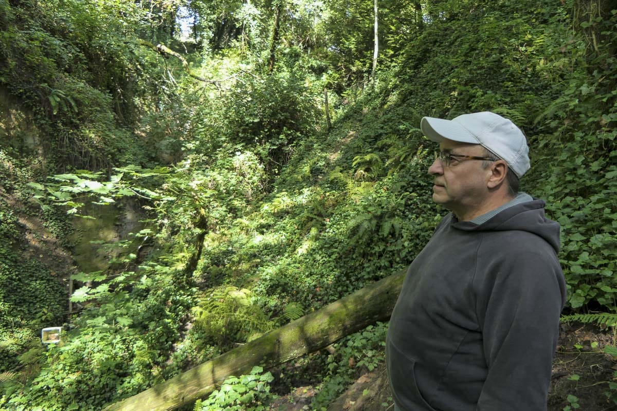 Area resident Peter Bracchi looks at garbage in a ravine at Arnold Park in Vancouver. Photo by Chris Brown