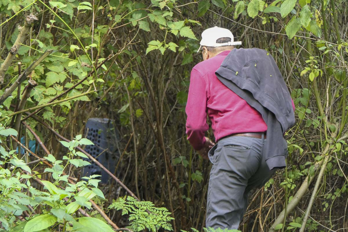 Peter Bracchi of Vancouver checks out an abandoned homeless campsite along Burnt Bridge Creek in Vancouver's Arnold Park. Photo by Chris Brown