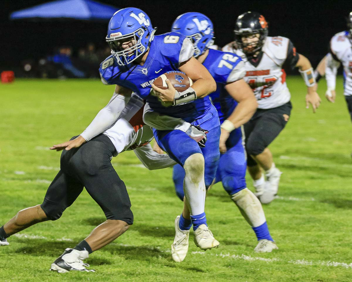 La Center quarterback Tom Lambert (6) breaks an attempted tackle by a Kalama defender during the Wildcats' 36-8 victory over Kalama Friday at La Center High School. Lambert finished with two touchdowns rushing and two more passing in the win. Photo by Mike Schultz