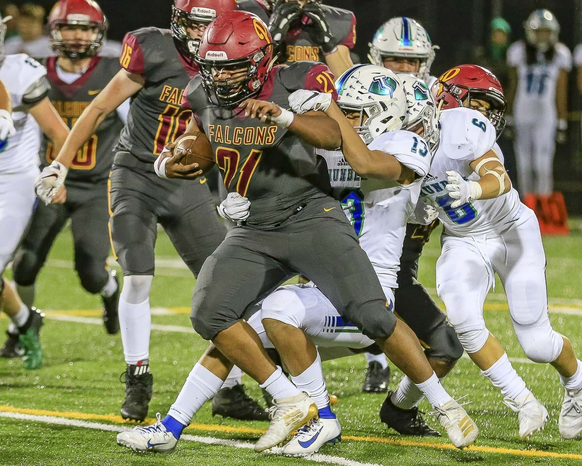 Prairie running back Devante Clayton (21) drags Mountain View tackler Kyle Chen (13) during Thursday's game at District Stadium in Battle Ground. Clayton scored a touchdown and added a 2-point conversion to tie the game at 16-16 in the third quarter. Photo by Mike Schultz