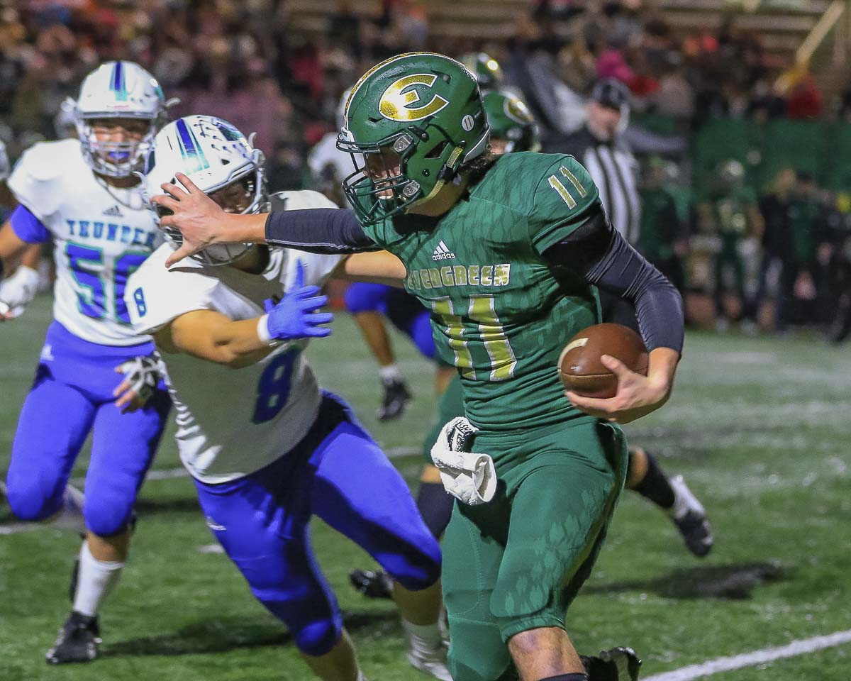Evergreen quarterback Carter Monda (11) uses a stiff arm in an attempt to elude Mountain View defender Dominic Stephens (8) during Evergreen's 40-35 victory over the Thunder in Class 3A Greater St. Helens League action Friday at McKenzie Stadium. Photo by Mike Schultz