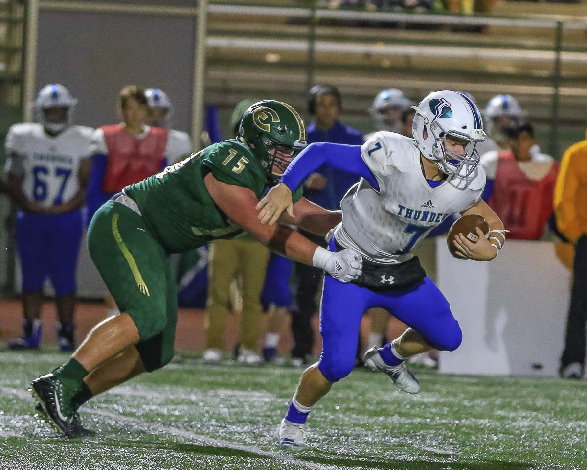 Mountain View quarterback Riley McCarthy (7) tries to break away from Evergreen's Nathan Lien (75) during Friday's game at McKenzie Stadium. McCarthy had three touchdown runs and two touchdown passes in his team's loss to Evergreen. Photo by Mike Schultz