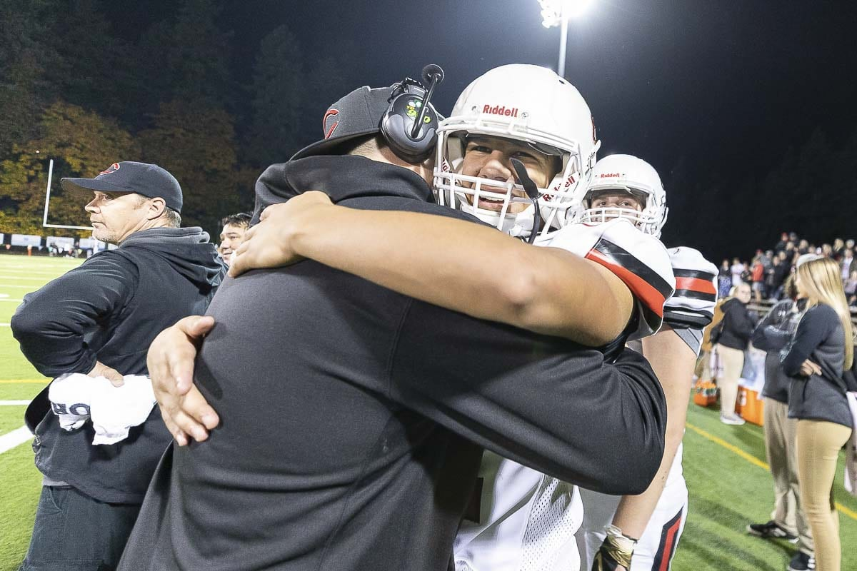 Camas linebacker Logan Silva celebrates the Papermakers' 21-17 victory over Skyview Thursday with an embrace with a member of the Camas coaching staff. Photo by Mike Schultz