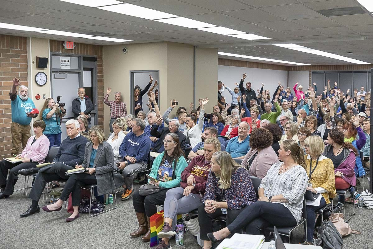 The crowd at Monday's Battle Ground School District Board of Directors meeting holds up their hands in opposition to a new proposed comprehensive sexual education curriculum for high school students. Photo by Mike Schultz