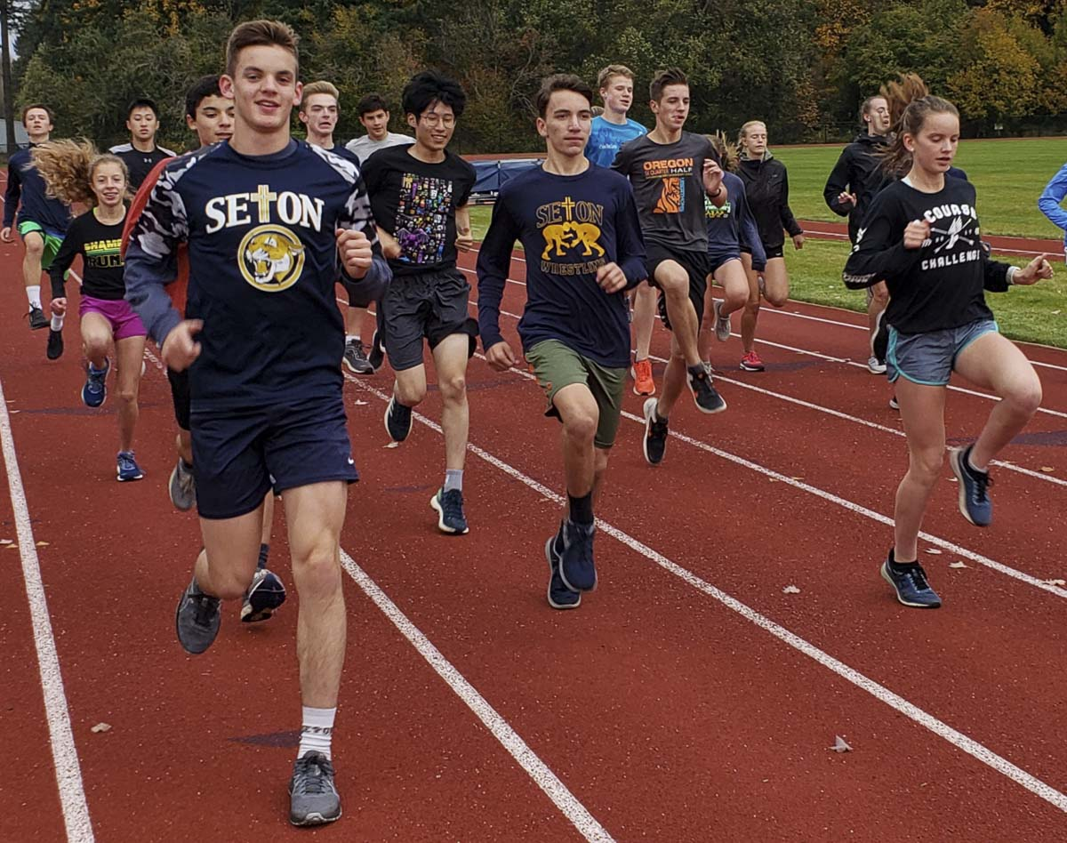 Seton Catholic's David Carrion (center, wearing the Seton shirt) and his younger sister Lara, to his left, are among the state's top runners in Class 1A. But they think team first. A year ago, the girls and boys teams both qualified for state, as teams. Photo by Paul Valencia