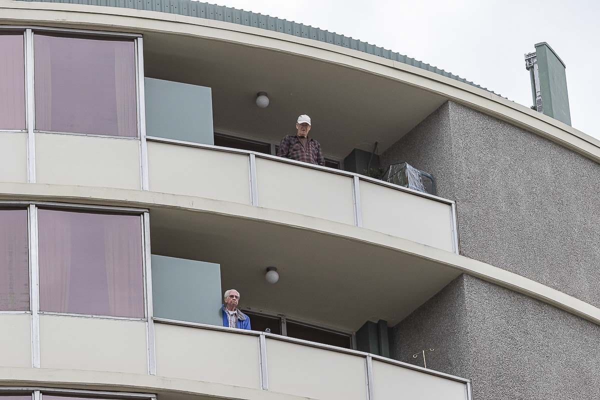 Unidentified residents of Smith Tower look out from rooms above where an active shooter was holed up Thursday. Photo by Mike Schultz