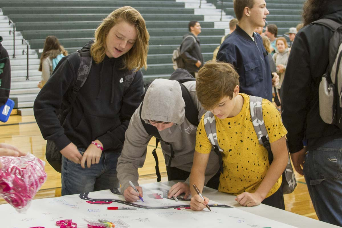 After the presentation, WHS students lined up to sign a banner pledging not to drive distracted. Photo courtesy of Woodland Public Schools