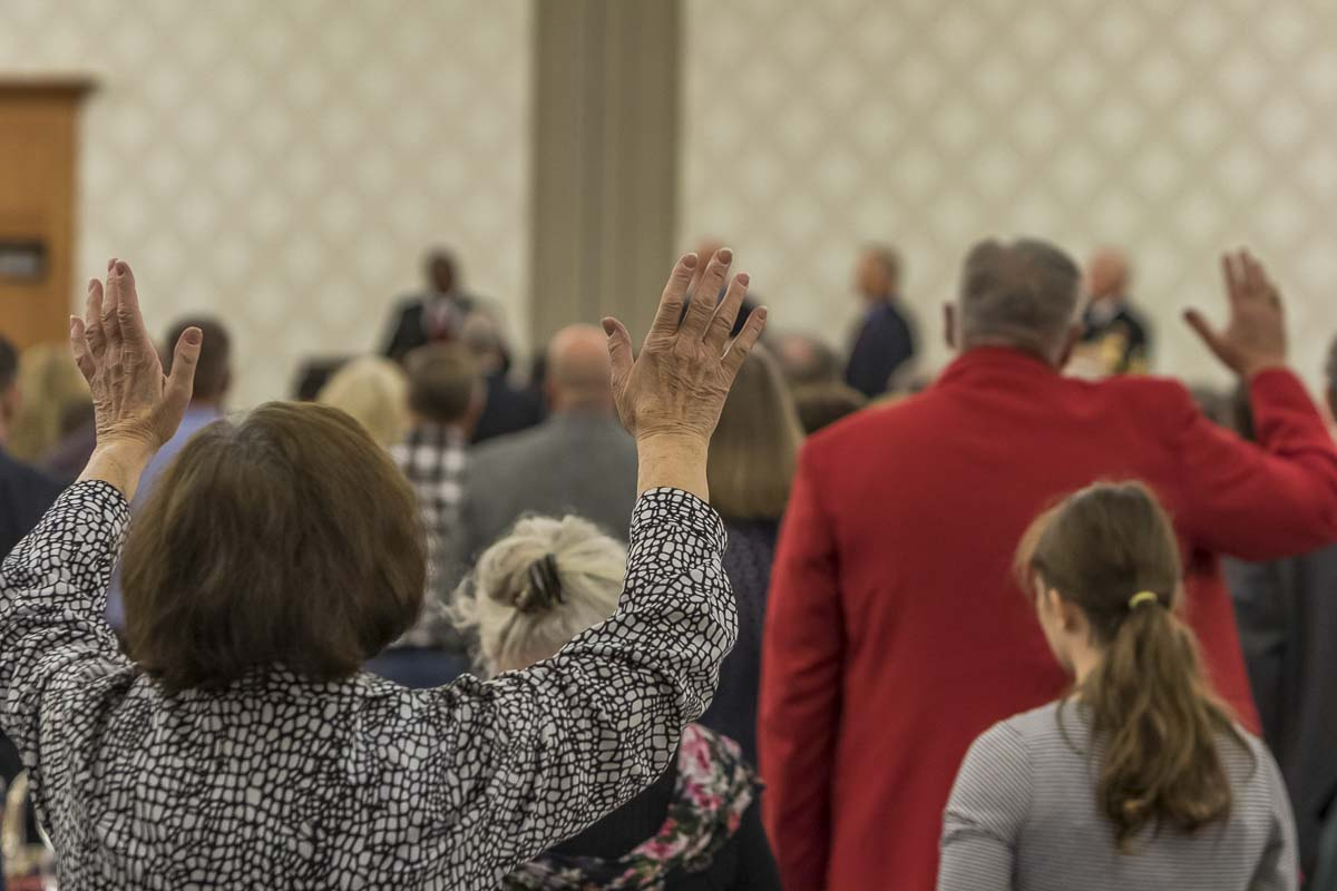 Praise and worship at the 2016 Clark County Prayer Breakfast is lead by Vancouver Police Officer Rey Reynolds (center background). Photo by Mike Schultz