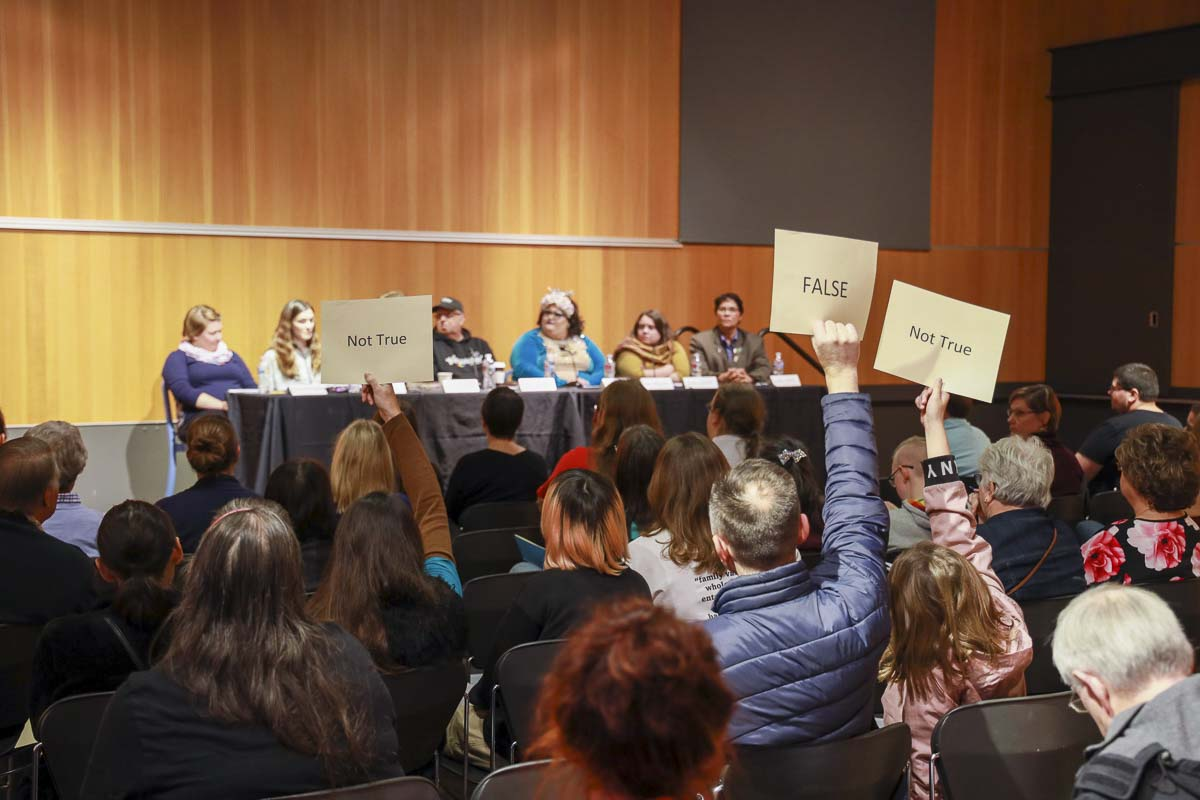 People opposed to Drag Queen Story Hour at Vancouver Community Library hold up signs during a panel on the events put on by the Fort Vancouver Regional Library. Photo by Chris Brown