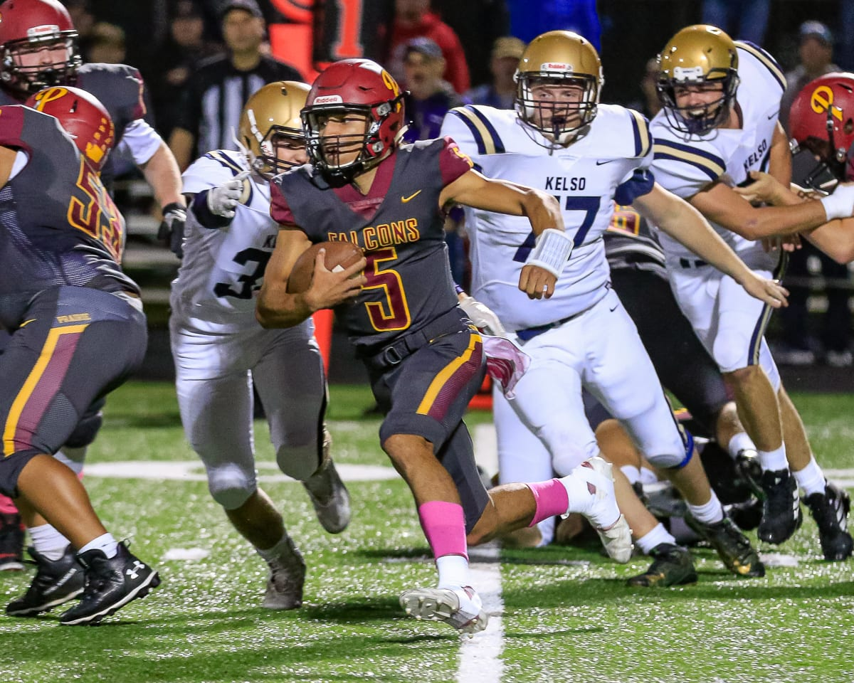 Prairie quarterback A.J. Dixson (5) races past Kelso defenders during the Falcons' 38-22 victory Friday at District Stadium in Battle Ground. Dixson ran for two touchdowns as Prairie remained undefeated on the season. Photo by Mike Schultz