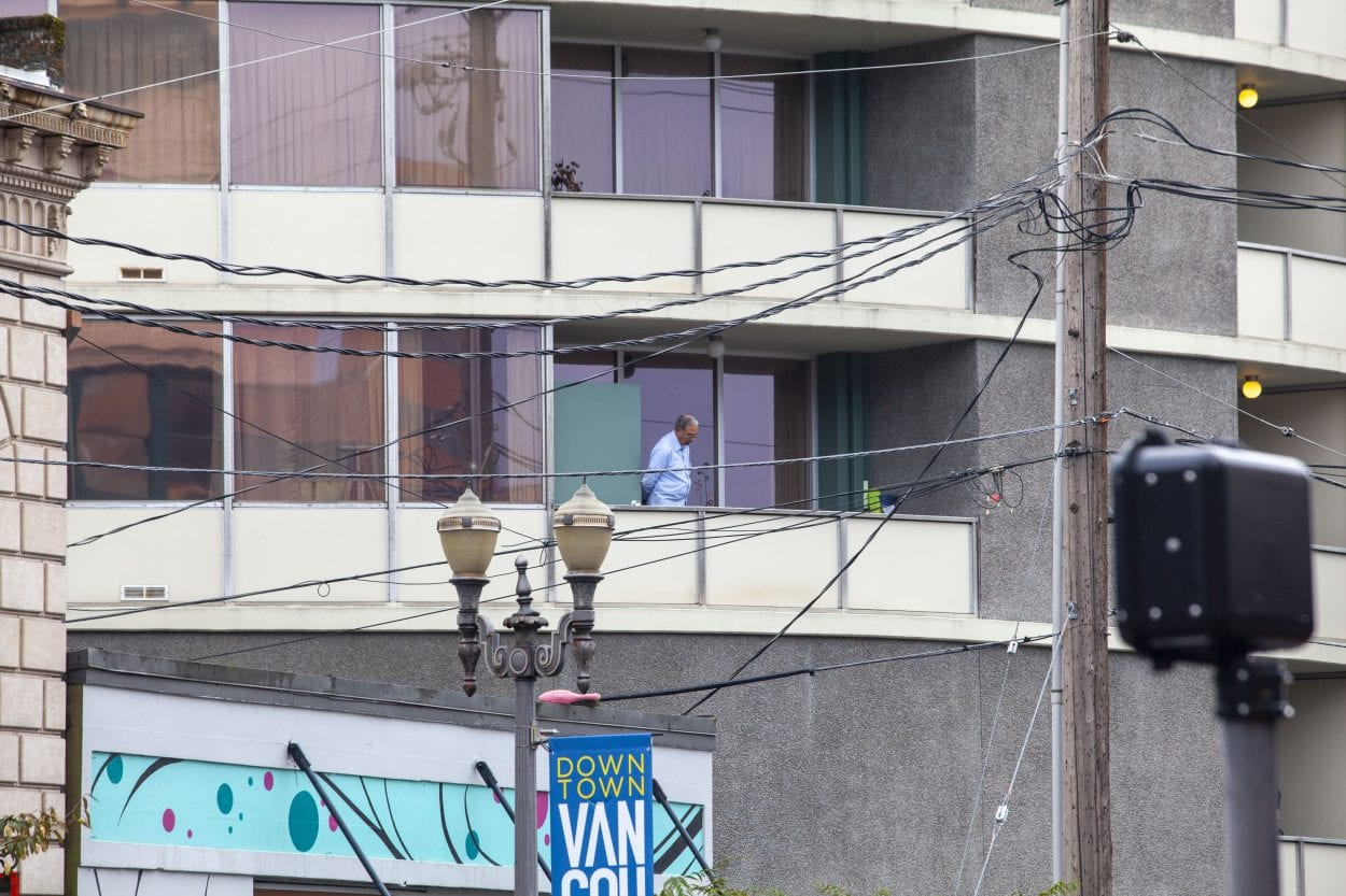 An unidentified man appears on a balcony at Smith Tower in downtown Vancouver where a shooting took place with multiple victims Thursday afternoon. Photo by Johnny Driver