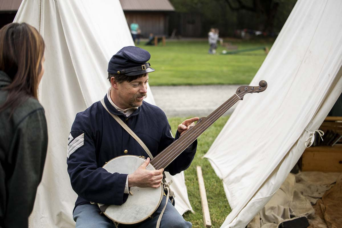 Reenacters at the Civil War camp weekend at Pomeroy Farm's Pumpkin Lane, teach visitors how to play period instruments including the banjo. Photo by Bailey Granneman