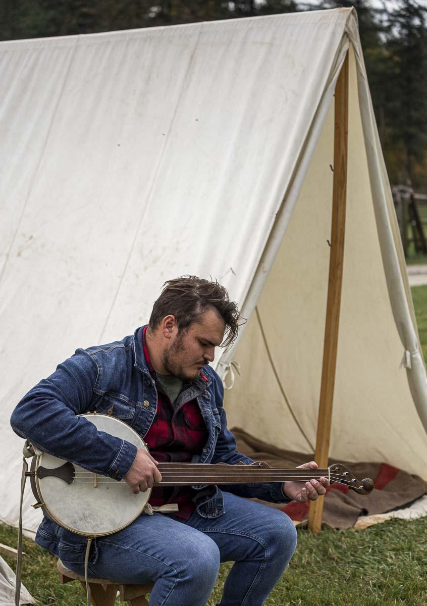 Skyler Savala of Vancouver takes a stab at playing a Civil War-era banjo while visiting the Civil War camp reenactment at Pomeroy Farm's Pumpkin Lane. Photo by Bailey Granneman