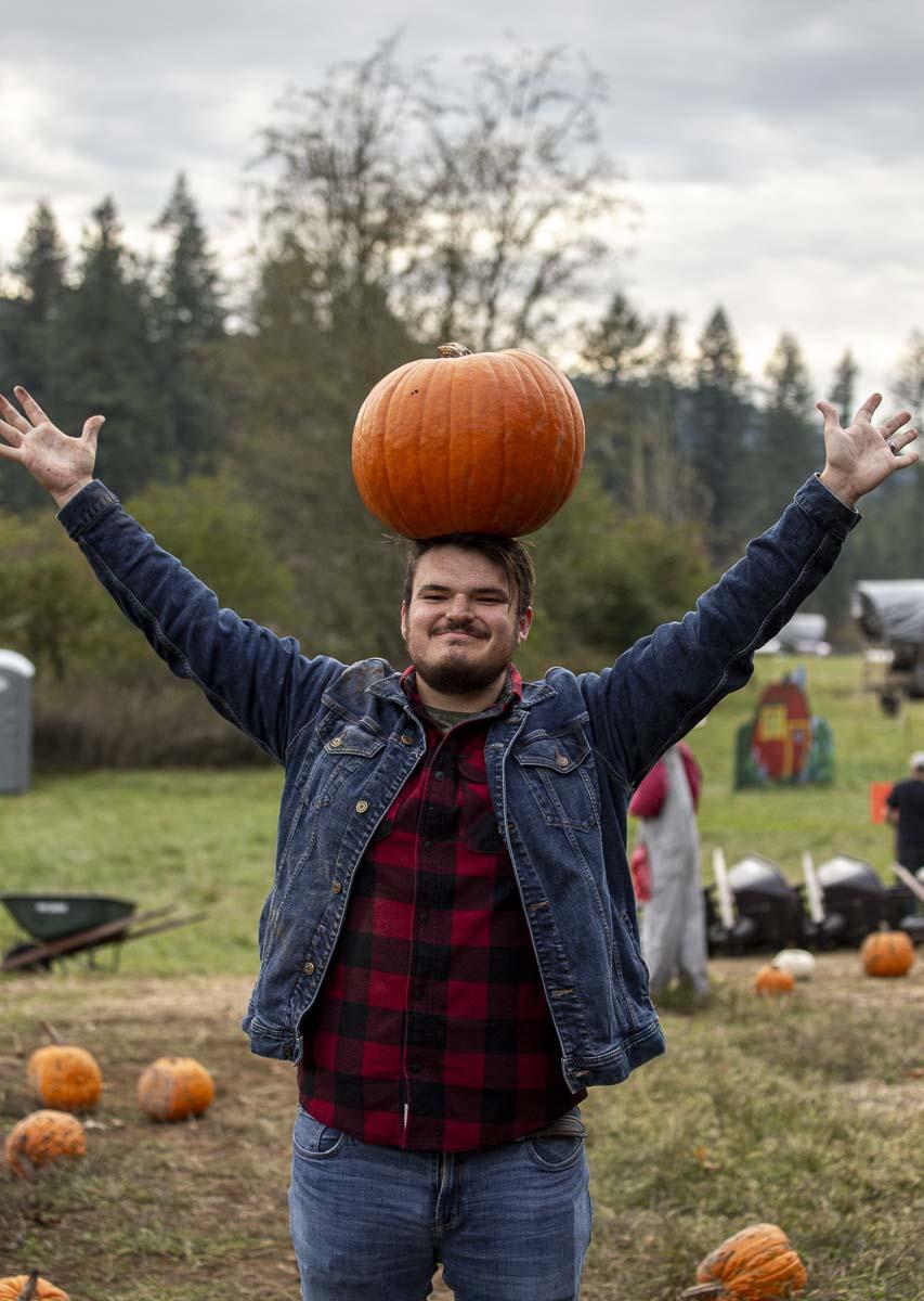 Skyler Savala balances his chosen pumpkin atop his head at Pomeroy Farm's Pumpkin Lane of 2019. Photo by Bailey Granneman