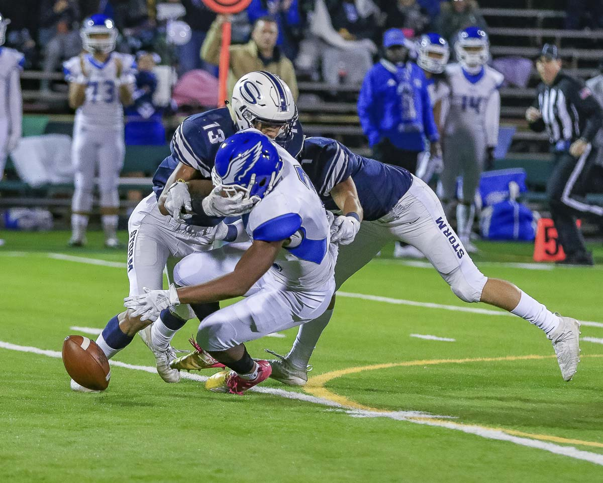Skyview defenders Xavier Owens (13) and Michael Stromberg (1) break up an attempted pass to a Federal Way defender during a lopsided victory by the Storm Friday at Kiggins Bowl. Photo by Mike Schultz