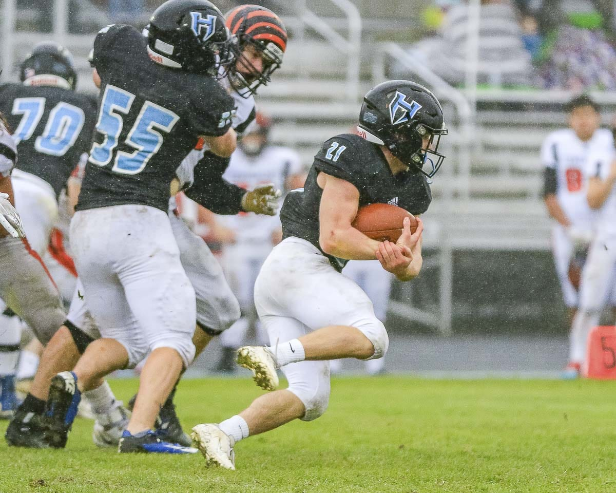 Hockinson running back Daniel Thompson (21) takes off on a touchdown run while Troy Visnius (55) provides a key block in the third quarter of the Hawks' playoff victory over Centralia Saturday at Hockinson High School. Thompson finished with 118 yards rushing for the Hawks. Photo by Mike Schultz