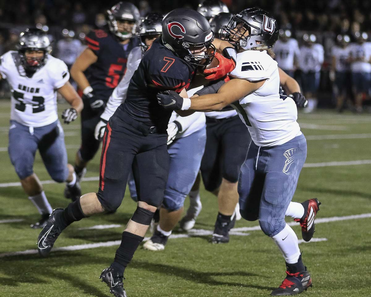 Camas running back Tyler Forner (7) fights for yardage Friday night. Forner had two touchdown runs as the Papermakers claimed the 4A GSHL title with a 28-14 win over Union. Photo by Mike Schultz