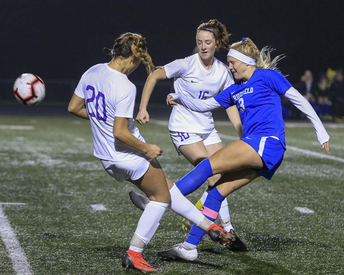 Annika Farley gets the ball past two Sequim defenders during their match Tuesday. Farley and the Spudders are going to the state quarterfinals. Farley also is expected to sign with the University of Portland on Wednesday. Photo by Mike Schultz