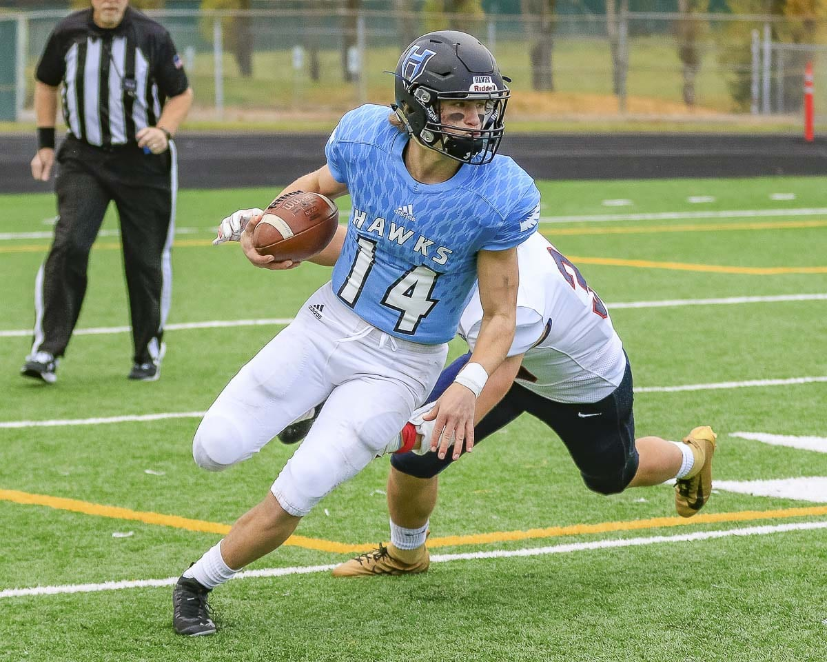 Hockinson quarterback Levi Crum (14) proved his value as a dual threat running and throwing the football Saturday as the two-time defending Class 2A champion Hawks advanced to the quarterfinals with a victory over Ellensburg. Photo by Mike Schultz
