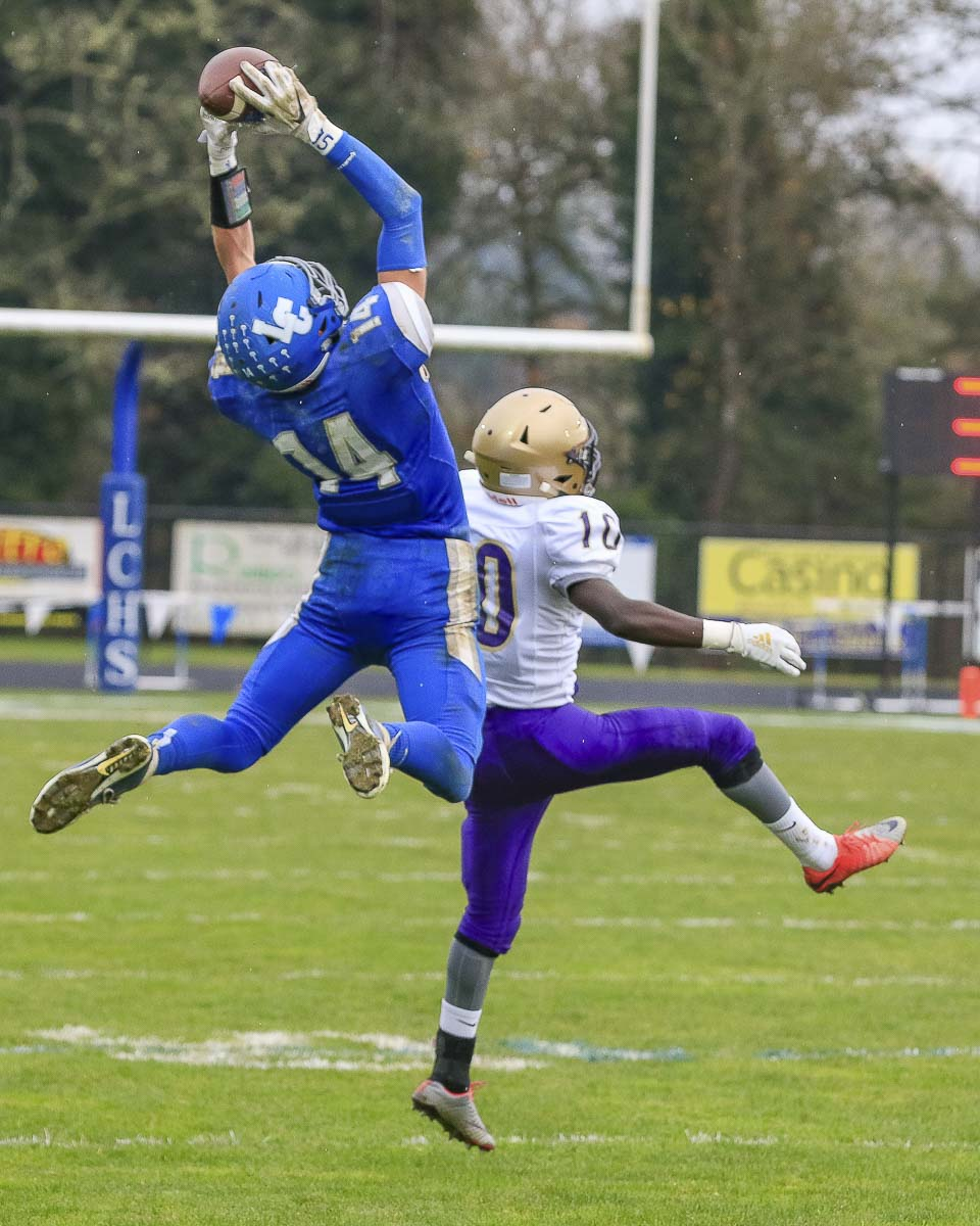 La Center's Andrew Scott (14) leaps high for a catch during Saturday's state playoff game against Connell at La Center High School. Photo by Mike Schultz
