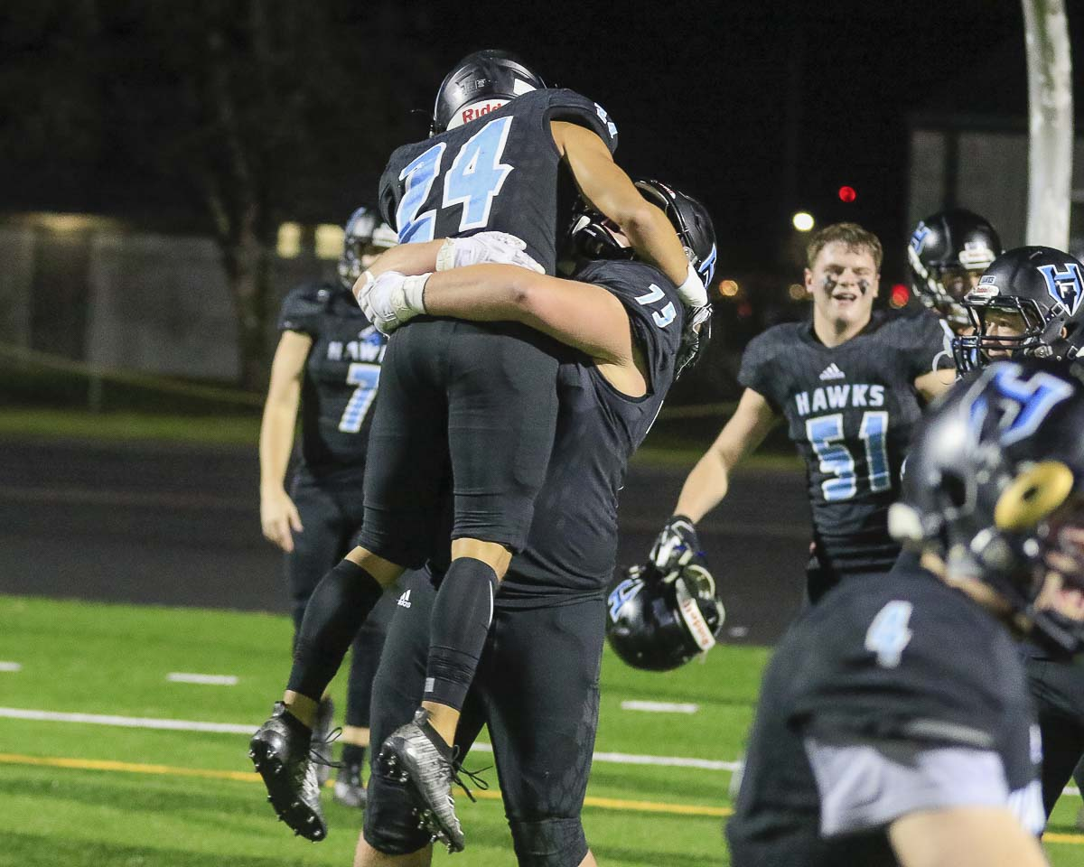 Hockinson's Jake Rogers (75) lifts teammate Makaio Juarez (24) in jubilation after the Hawks earned a trip to the Class 2A state semifinals with a 29-28 victory over Lakewood Saturday at District Stadium in Battle Ground. Photo by Mike Schultz