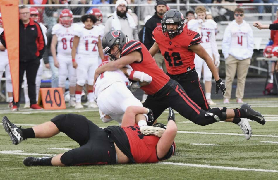 Robert Silva (on the ground), holds on to an Eastmont ball carrier as Jairus Phillips closes in to finish the tackle during Camas' 41-0 win Saturday. The Camas defense shined all day against the Wildcats. Photo courtesy of Kris Cavin
