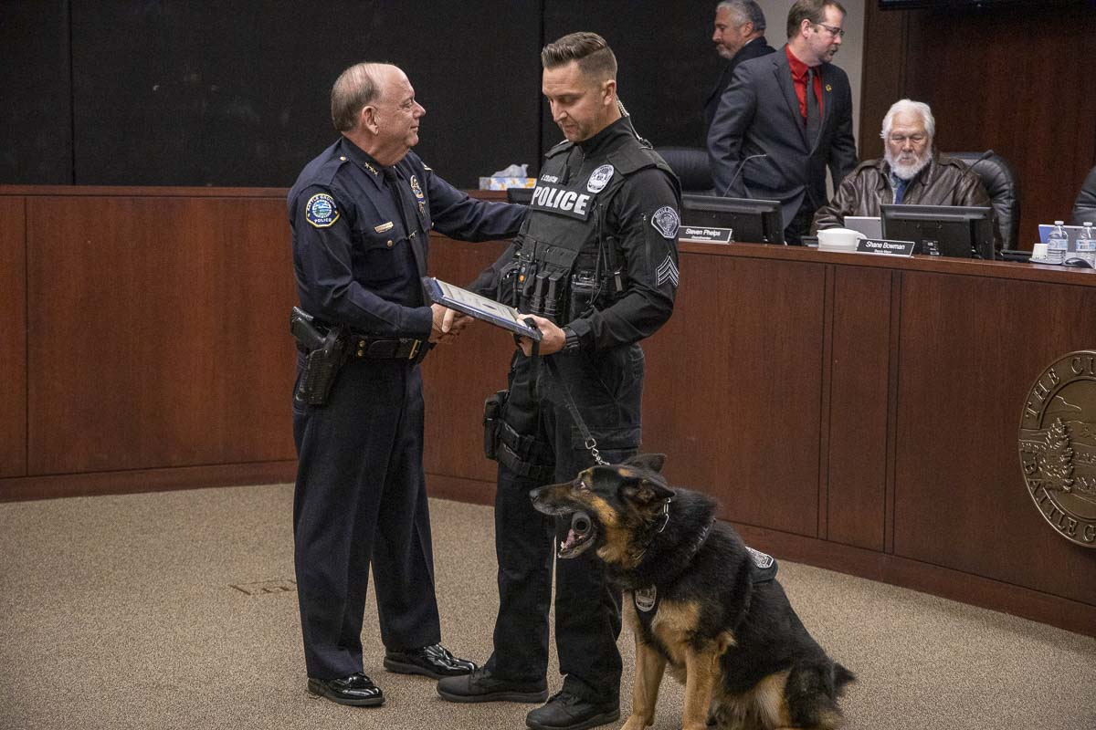 K-9 officer Luca and his handler, Sgt. Chris Crouch, receive a plaque from Battle Ground Police Chief Bob Richardson at Monday's city council meeting. Luca is retiring after six years with the force. Photo by Chris Brown