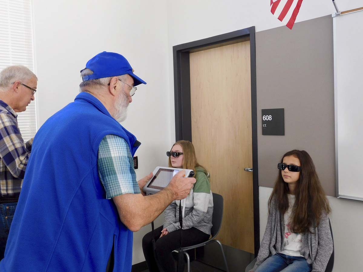Members of the Ridgefield Lions Club conduct vision screenings for students at View Ridge Middle School. Students wear special glasses as part of the procedure. Photo courtesy of Ridgefield Public Schools