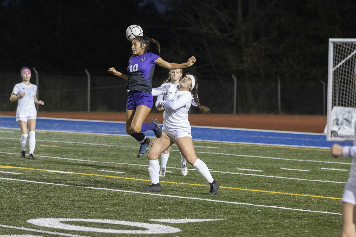 Columbia River's Yaneisy Rodriguez (10) heads the ball while Hockinson's Ellie Summerson (16) defends. Photo courtesy of Alan Moditz