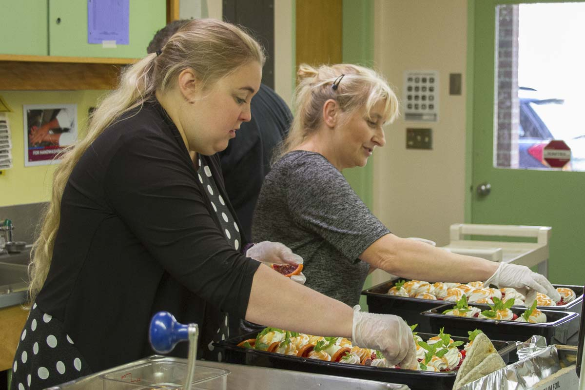 The district's head of Nutrition Services, Laura Perry (left), organizes and manages the event which includes designing the menu, helping prepare the food, assisting with serving, and teaching students before the event. Photo courtesy of Woodland Public Schools