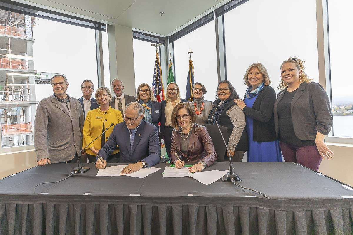 Governor Jay Inslee of Washington State and Oregon Governor Kate Brown sign a Memorandum of Intent over the Interstate 5 Bridge, with Southwest Washington elected officials gathered behind them. Photo by Mike Schultz