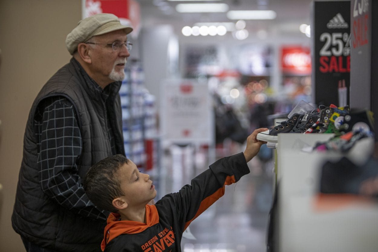 Roger Martin (left) helps Vinnie Castiglione find new shoes during the 2019 Santa Clothes event at JC Penny in the Vancouver Mall. Photo by Jacob Granneman