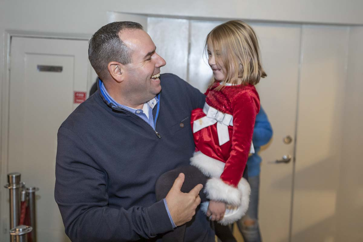 Cano Real Estate Owner/Broker Nathan Cano enjoys some Christmas cheer with a happy youngster at the Cano Real Estate Customer Appreciation Night. Photo by Mike Schultz