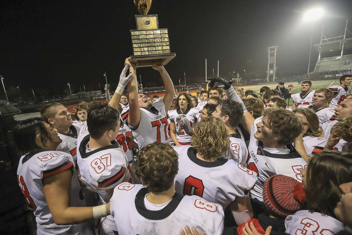 Camas lineman Caadyn Stephen (77) gets his turn to hoist the championship trophy while his teammates celebrate the moment around him. Photo by Mike Schultz