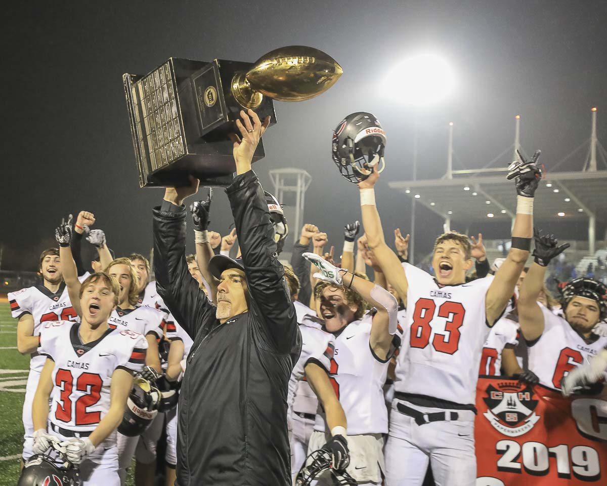 Camas coach Jon Eagle holds up the trophy after his Papermakers claimed the Class 4A state high school football championship Saturday. Photo by Mike Schultz