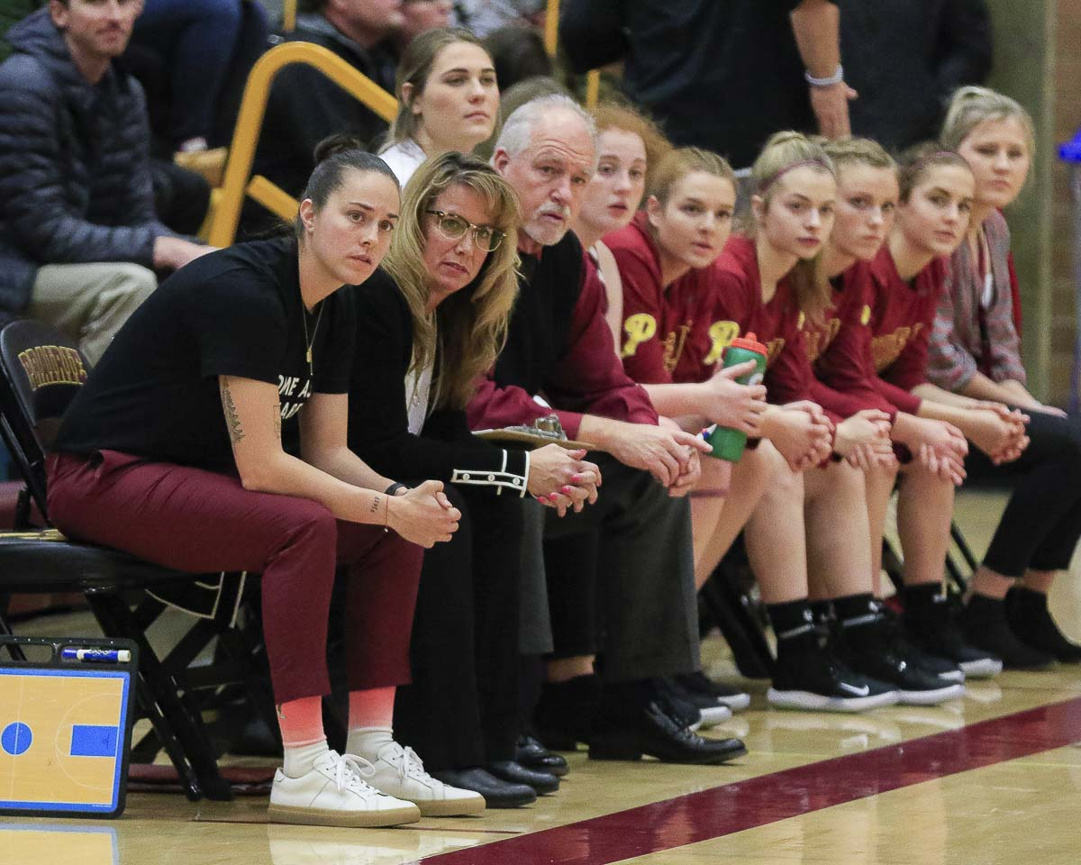 Ashley Corral, far left, sits next to her mother, Hala, as they watch the Prairie Falcons play in a recent game. Hala is the head coach, Ashley is an assistant, and Allison Corral is playing her senior season with the Falcons. Photo by Mike Schultz