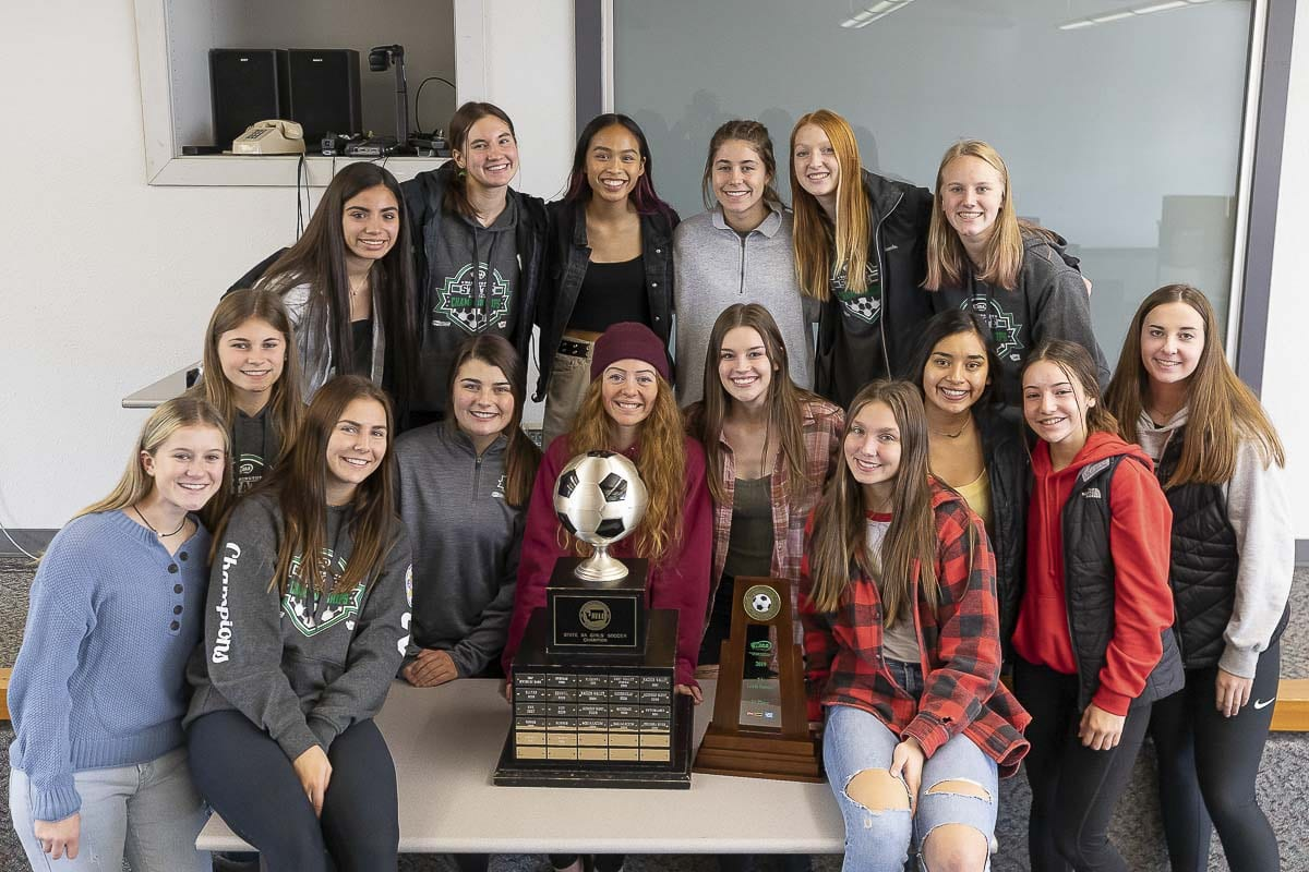 Some members of the Columbia River girls soccer team pose with the state championship trophy. Photo by Mike Schultz