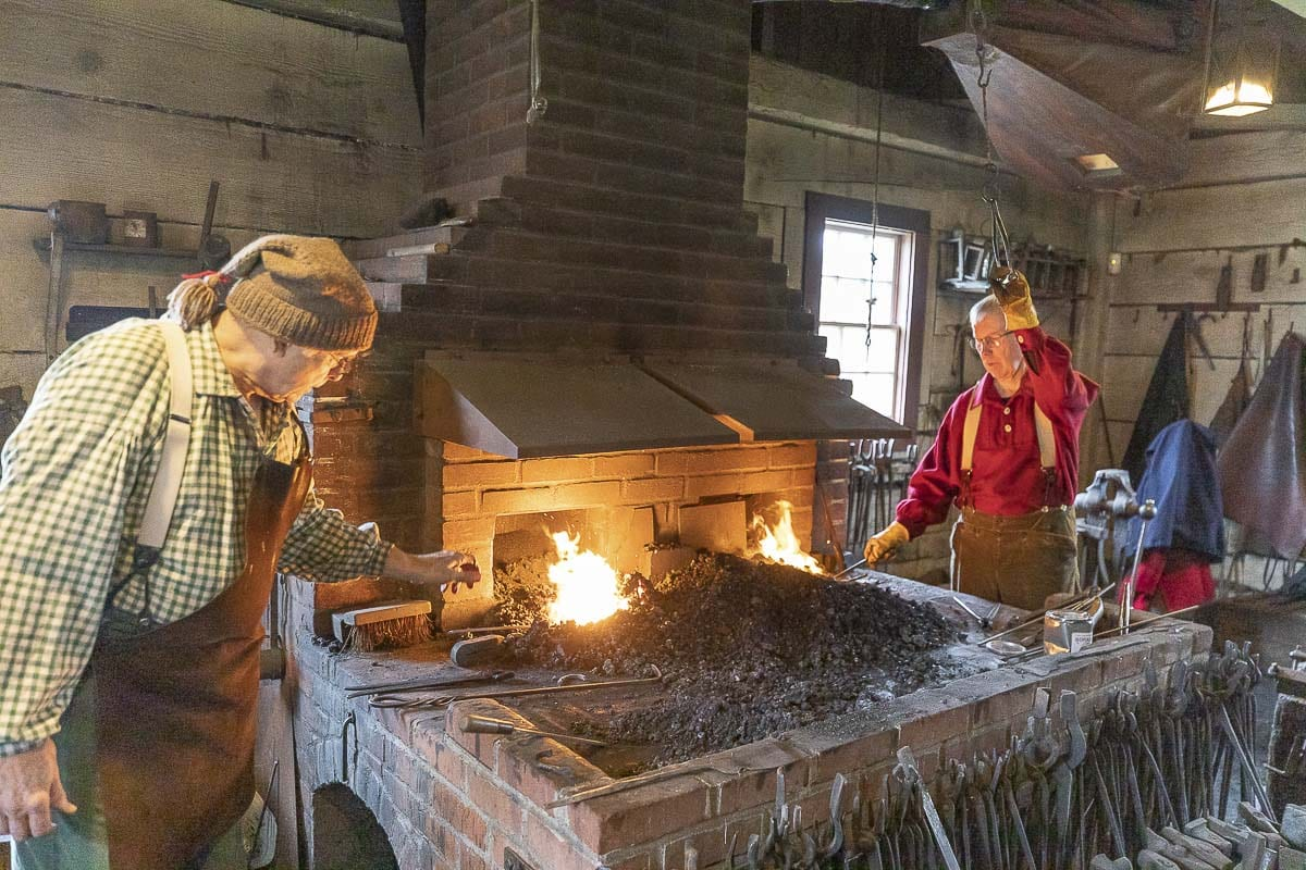 Clay Ford (left) and Tom Dwyer operate bellows to heat iron in the blacksmith shop at the Christmas at Fort Vancouver event Saturday. Photo by Mike Schultz