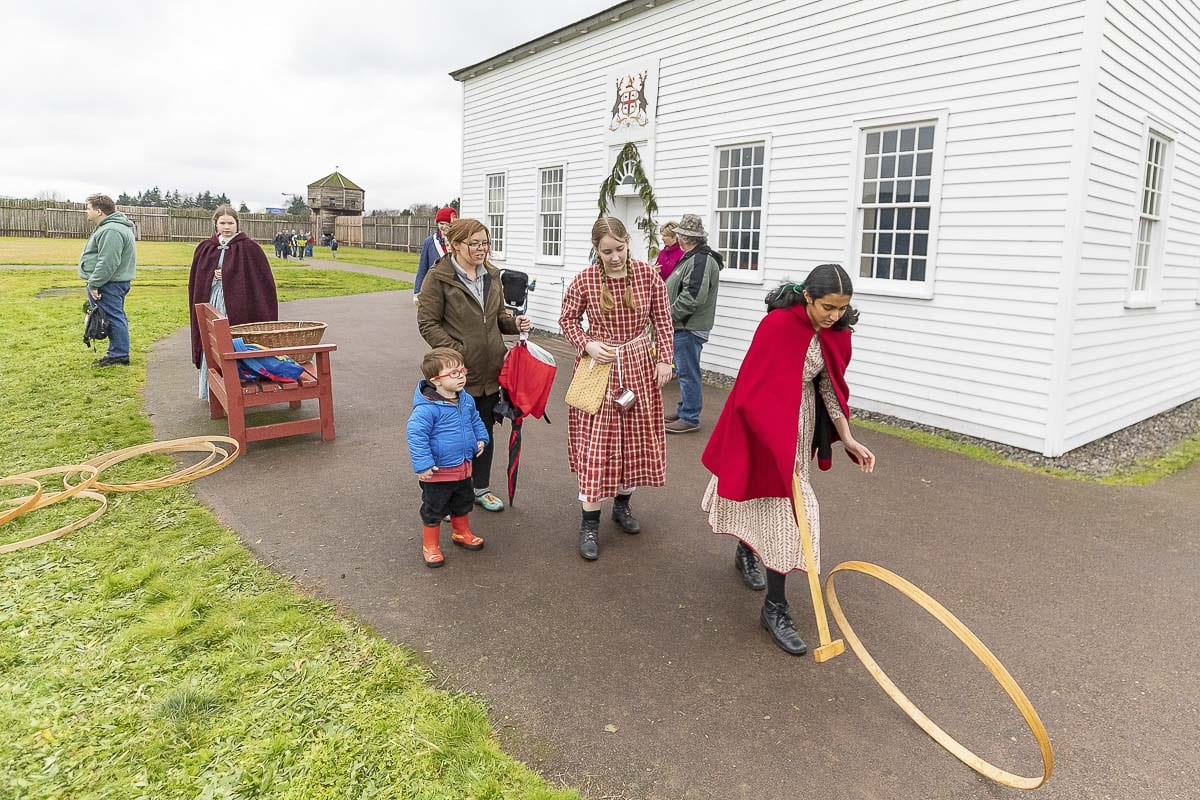 Some of the younger attendees at Saturday's Christmas at Fort Vancouver event play a game with a hoop and a stick. Photo by Mike Schultz