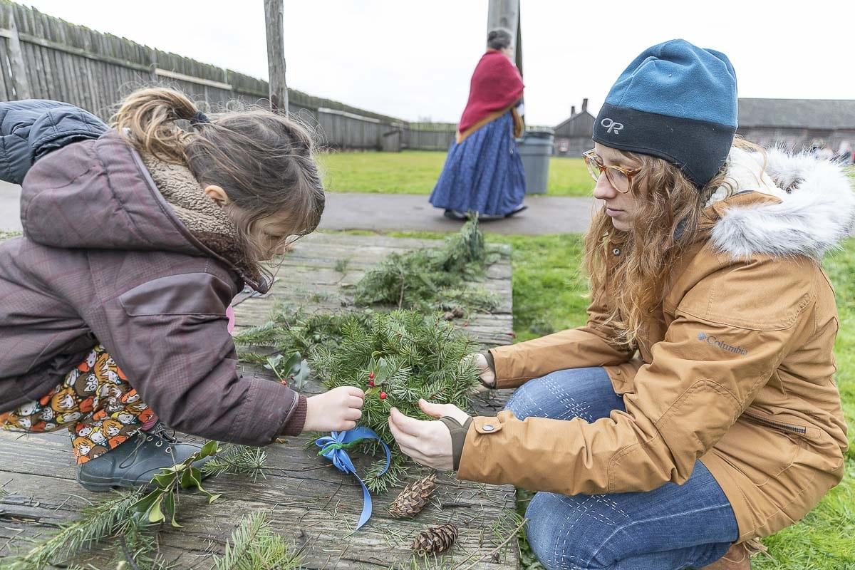 Penny and Havalah Turner participate in the wreath-making activity Saturday at the Christmas at Fort Vancouver event. Photo by Mike Schultz